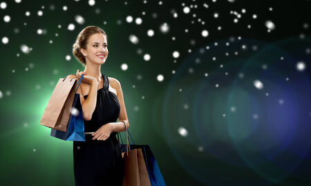 holydays: luxury, holydays, people and sale concept - smiling woman with shopping bags over snow and night lights background
