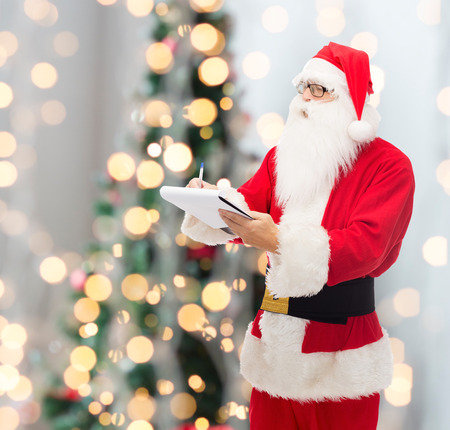 christmas, holidays and people concept - man in costume of santa claus with notepad and pen over tree lights background photo
