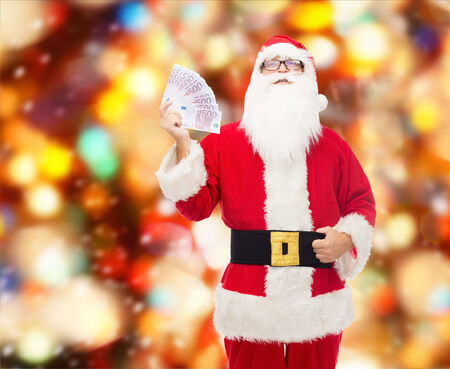 christmas profits: christmas, holidays, winning, currency and people concept - man in costume of santa claus with euro money over red lights background