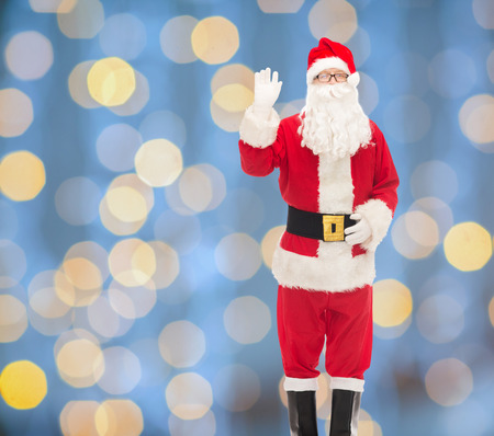 christmas, holidays, gesture and people concept - man in costume of santa claus waving hand over blue lights background photo