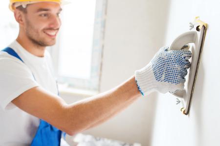 house painter: negocio, construcci�n, profesi�n y concepto de la gente - constructor sonriente con rectificado herramienta de interiores