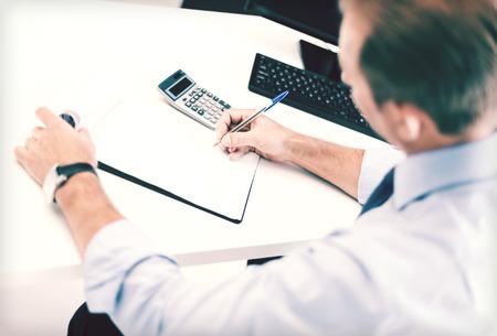 affaires, le bureau, l'école et le concept de l'éducation - homme d'affaires avec ordinateur portable et une calculatrice