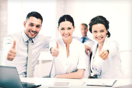 business concept - business team showing thumbs up in office photo