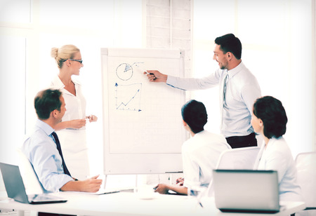 business concept - business team working with flipchart in office Stock Photo