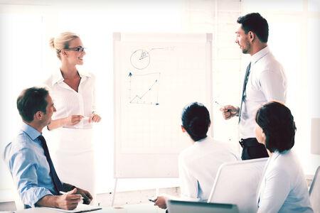 sourire équipe d'affaires travaillant avec un tableau de conférence dans le bureau