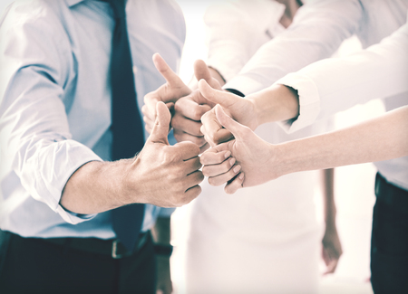 success and winning concept - happy business team showing thumbs up in office Stock Photo