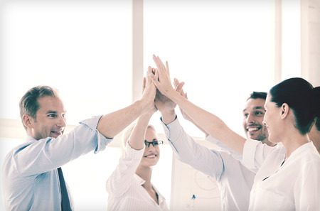 business success: success and winning concept - happy business team giving high five in office
