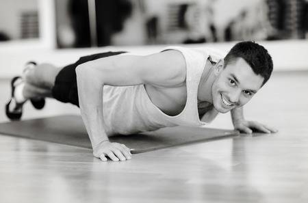 musculine: fitness, sport, training, gym and lifestyle concept - smiling man doing push-ups in the gym