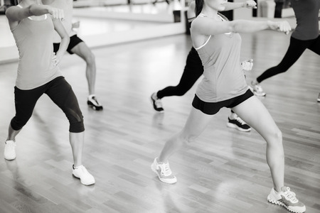 forme et sante: fitness, sport, formation, salle de gym et le concept de mode de vie - groupe de gens souriants avec un entraîneur exerçant dans le gymnase Banque d'images