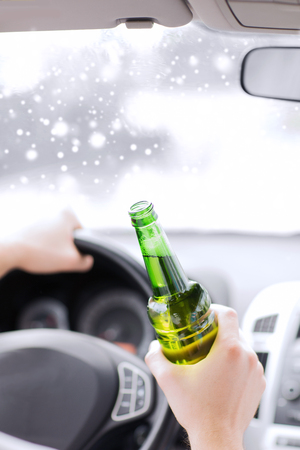 drinking driving: transportation, alcohol, vehicle and people concept - close up of man drinking alcohol while driving car Stock Photo