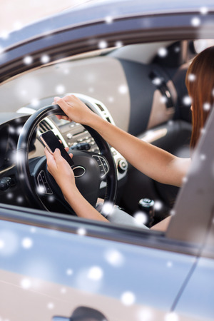 transportation, people, technology and vehicle concept - close up of woman using smartphone while driving car photo