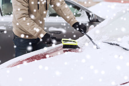 transportation, winter, people and vehicle concept - closeup of man cleaning snow from car with brush photo