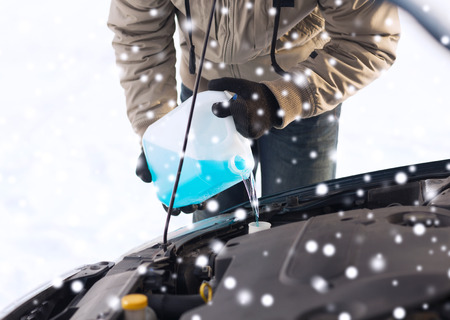 antifreeze: transportation, winter, people and vehicle concept - closeup of man pouring antifreeze into car Stock Photo