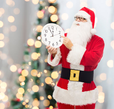 12 oclock: christmas, holidays and people concept - man in costume of santa claus with clock showing twelve pointing finger over tree lights background Stock Photo