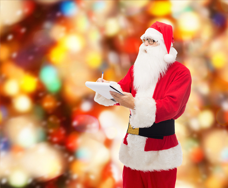 christmas, holidays and people concept - man in costume of santa claus with notepad and pen over red lights background photo