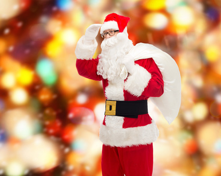 far away look: christmas, holidays and people concept - man in costume of santa claus with bag looking far away over red lights background Stock Photo