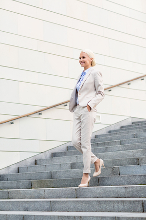 walking down: business, people and education concept - young smiling businesswoman walking down stairs outdoors Stock Photo