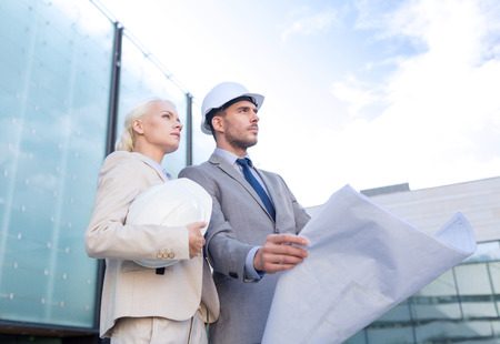business, partnership, architecture and people concept - businessman and businesswoman with blueprint and helmets on city street photo