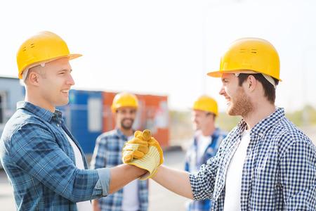 bedrijfsleven, de bouw, teamwork, gebaar en mensen concept - groep van lachende bouwers in bouwvakkers begroeten elkaar met een handdruk buitenshuis