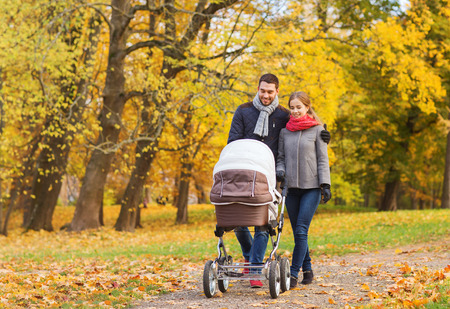 the fall: love, parenthood, family, season and people concept - smiling couple with baby pram in autumn park