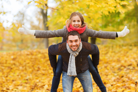 love, relationship, family and people concept - smiling couple having fun in autumn park Фото со стока