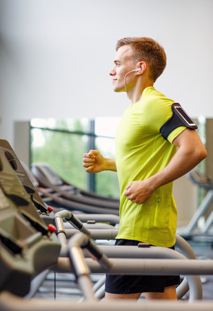 sport, fitness, lifestyle, technology and people concept - smiling man with smartphone and earphones exercising on treadmill in gym