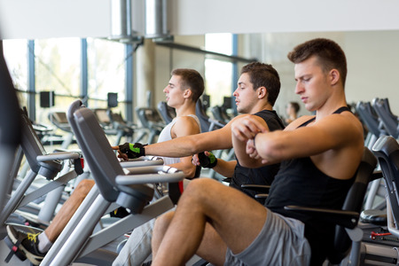 Men exercise: sport, fitness, lifestyle, technology and people concept - men working out on exercise bike in gym