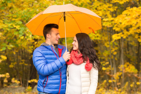 young happy couple: love, relationship, season, family and people concept - smiling couple with umbrella walking in autumn park