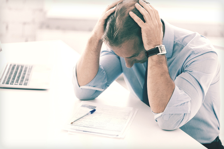 examination stress: business, office, school and education concept - stressed businessman with papers at work