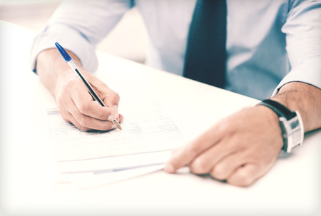 new contract: business, office, school and education concept - man signing a contract