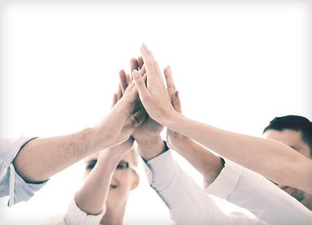 trabajo en equipo: el éxito y el concepto ganador - equipo de negocios feliz dando de alta cinco en la oficina Foto de archivo