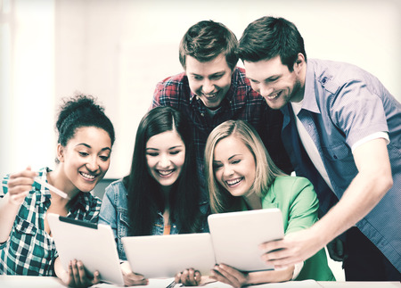 classmates: education and internet - smiling students looking at tablet pc in lecture at school Stock Photo