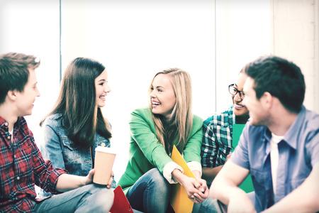 personas platicando: concepto de la educación - los estudiantes comunicarse y riendo en la escuela Foto de archivo