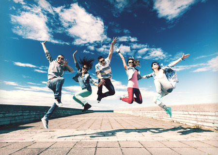 summer, sport, dancing and teenage lifestyle concept - group of teenagers jumping Banco de Imagens