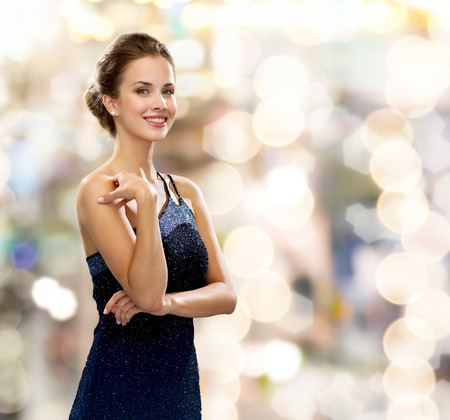 evening dress: people, holidays and glamour concept - smiling woman in evening dress over lights background
