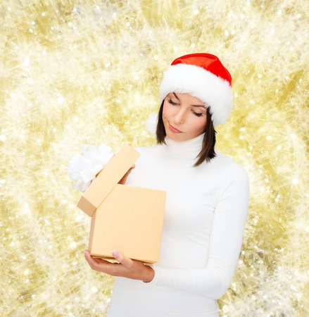 christmas, winter, happiness, holidays and people concept - woman in santa helper hat with gift box over yellow lights background photo