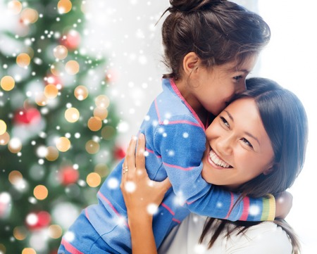 preteen asian: childhood, happiness, christmas, family and people concept - smiling little girl and mother hugging indoors over living room with tree