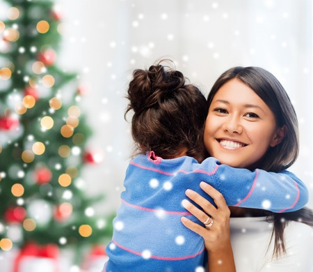 childhood, happiness, christmas, family and people concept - smiling little girl and mother hugging over living room with tree photo