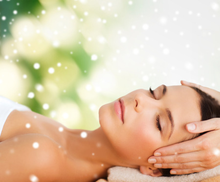 treatment: beauty, health, holidays, people and spa concept - beautiful woman in spa salon getting face or head massage over green background