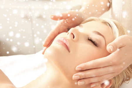 eye care professional: beauty, health, holidays, people and spa concept - beautiful woman in spa salon getting face or head massage Stock Photo