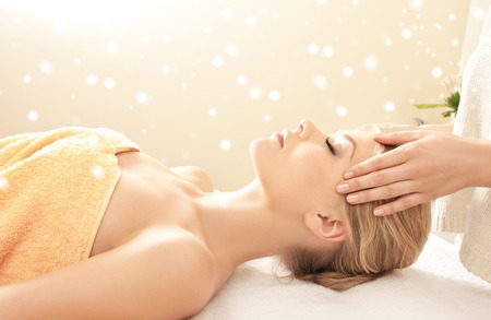 salon spa: beauty, health, holidays, people and spa concept - beautiful woman in spa salon getting face or head massage Stock Photo
