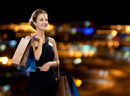 happy customer: shopping, sale, gifts and holidays concept - smiling woman in dress with shopping bags over black background
