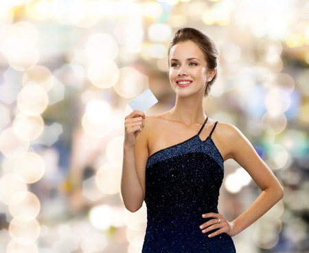 shopping, wealth, holidays and people concept  - smiling woman in evening dress holding credit card over lights background