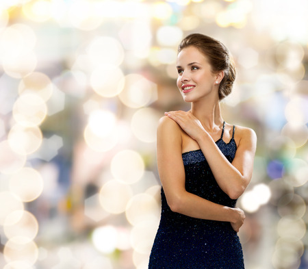 mensen, vakantie en glamour concept - glimlachende vrouw in avondjurk op achtergrond verlichting Stockfoto