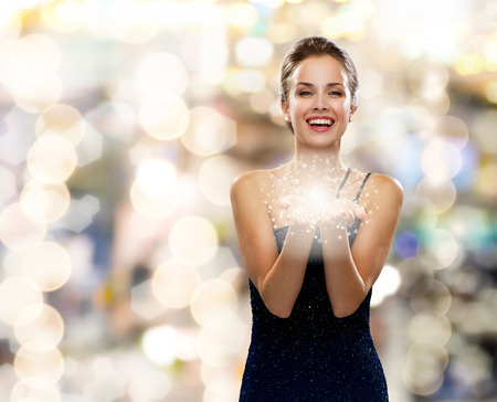 holidays and people concept - laughing woman in evening dress holding something over lights background