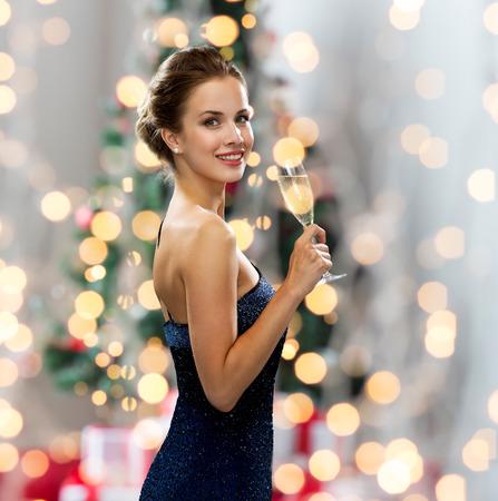sektglas: Party, Getränke, Urlaub, Menschen und Feier-Konzept - lächelnde Frau im Abendkleid mit einem Glas Sekt über Weihnachtsbaum Lichter Hintergrund Lizenzfreie Bilder