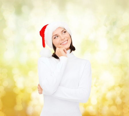 santa helper: christmas, holidays, winter, happiness and people concept - thinking and smiling woman in santa helper hat over yellow lights background