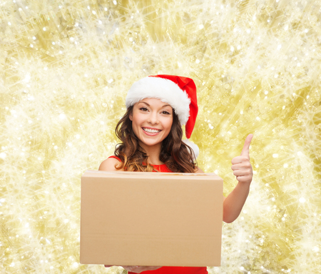 approvement: christmas, winter holidays, delivery, gesture and people concept - smiling woman in santa helper hat with parcel box showing thumbs up over yellow lights background