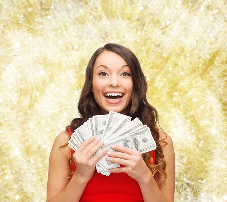 クリスマス、販売、銀行業、勝利および休日のコンセプト - 笑顔私たちと赤いドレスを着た女性ドルお金黄色のライトを背景に