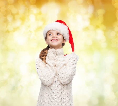 christmas, holidays, childhood and people concept - smiling girl in santa helper hat over yellow lights background photo